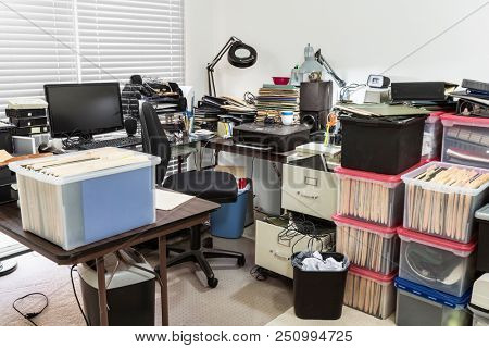 Messy business office with cluttered desk and boxes full of files.