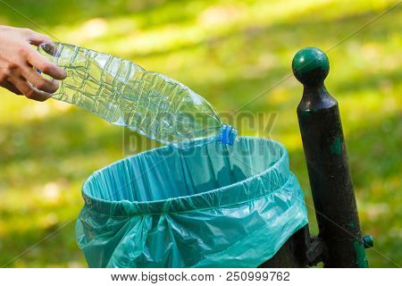 Hand Of Woman Throwing Plastic Bottle Into Trash Can, Concept Of Environmental Protection, Littering