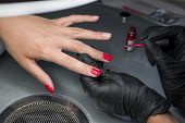 Woman having a nail manicure in a beauty salon with a closeup view of a beautician applying varnish with an applicator. Master painted nails with nail polish. Details shot of hands applying red nail poster