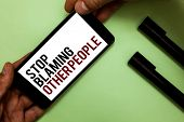 Text sign showing Stop Blaming Other People. Conceptual photo Do not make excuses assume your faults guilt Man's hand hold iPhone with black and red words near two black marker poster