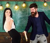 Girl on helpless face punished by teacher. Man with beard slapping sexy student, chalkboard on background. Schoolmaster punishes sexy student with slapping on her buttocks with book. Role game concept poster