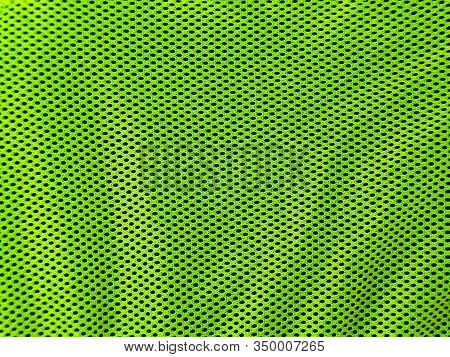 Background And Texture Of Perforated Light Green Fabric In Close-up. Perforated Fabric Background.
