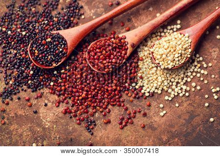 Red, black and white quinoa grains in a wooden spoon. Healthy food background. Seeds of white, red and black quinoa - Chenopodium quinoa. Vegetarian food