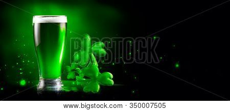 St. Patrick's Day Green Beer pint over dark green background, decorated with shamrock leaves. Patrick Day Irish pub party, celebrating. Glass of Green beer close-up. Border art design, Wide format