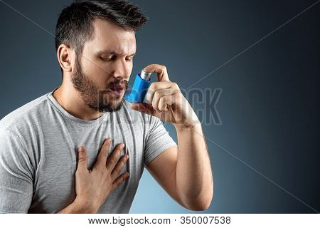 Portrait Of A Man With An Asthma Inhaler In His Hands, An Asthmatic Attack. The Concept Of Treatment