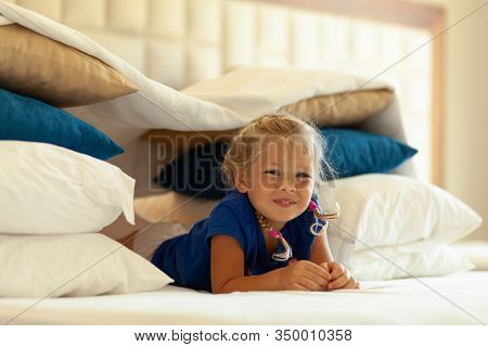 Little Cute Girl Built Impromptu Fort (castle, House) Out Of Pillows And Blankets On Bed. Children H