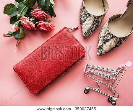 Red Leather Women Wallet, Roses, Shopping Cart And High Shoes On Pink Background. Top View, Shopogol