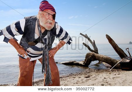 Ragged castaway pirate on beach bares his teeth and leans forward defending treasure chest nearby. poster