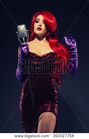 Young Beauty Redhead Woman With Very Long Hair In Red Gown With Microphone On The Stand On A Black B