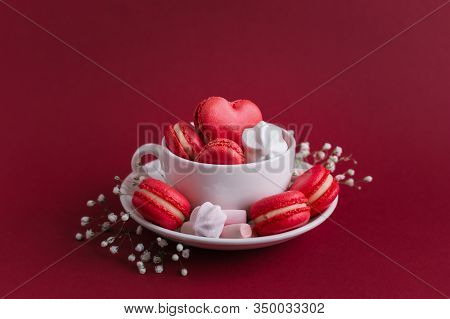 Valentine's Day Background With Red French Heart-shaped Macarons And Marshmallows. Cup With Macarons
