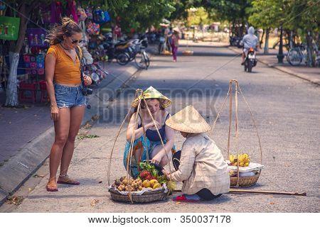 Hanoi, Vietnam - June 12, 2019: Old Quarter Of Hanoi. Street Sellers Sell Fruit In Traditional Hats