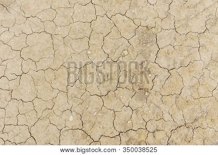 Texture Of Dry Cracked Earth Surface. Cracked Patch Of Land With No Vegetation From Above. Cracks In