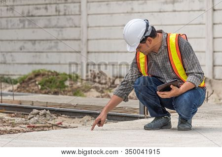 Asian Man Civil Construction Engineer Worker Or Architect With Helmet And Safety Vest Working And Ho