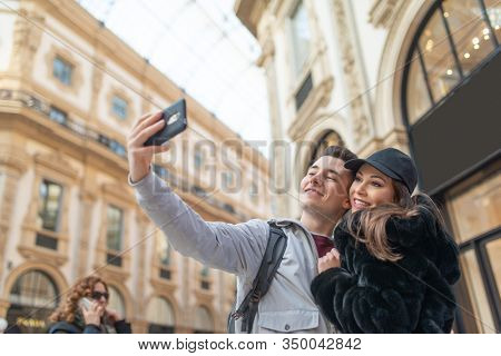 Couple of turists taking a selfie in the city of Milan, Italy