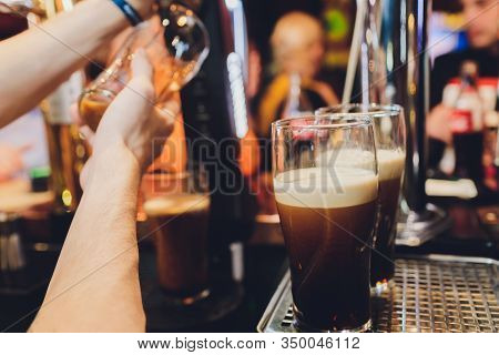 Barkeeper Pulling A Pint Of Beer Behind The Bar.