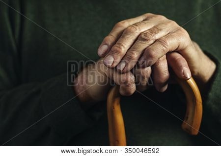 Hands Of A Senior Man Clasping A Cane