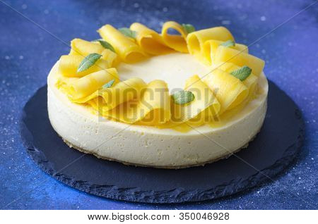 Cheesecake With Mango And Mint On A Blue Board