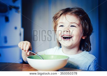 Kid Eating. Little Boy Having Breakfast In The Kitchen. Smiling Happy Adorable Baby Eating Fruit Mas