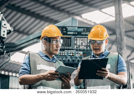 Two Asian Workers In Their 30s Talking In A Metal Fabrication Plant Wearing Hardhats And Protective