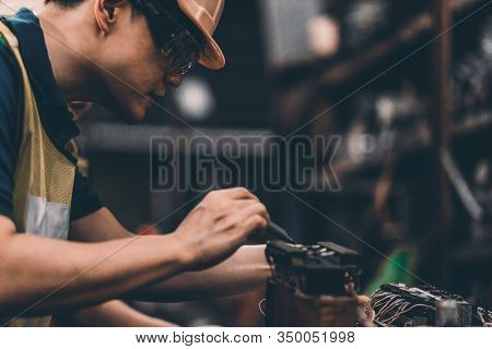 Closeup Side View Of Early 40's Male Employee At A Factory Plant Operating A Production Line Machine