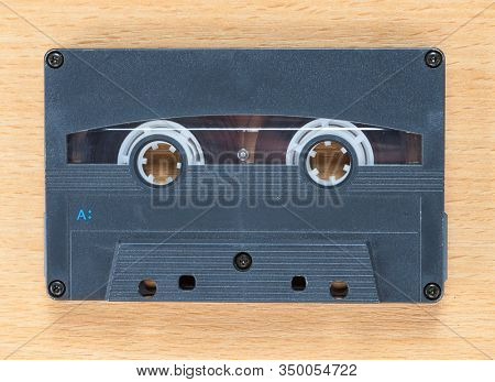 Compact audio cassette tape on a wooden background