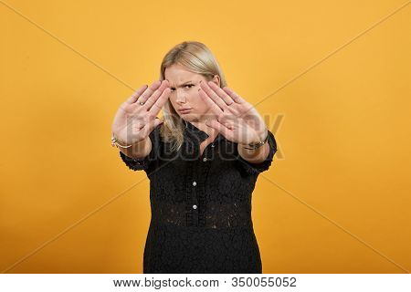Beautiful Blonde Girl In Black Dress On Yellow Background Irritated Angry Woman Stops With Her Hands
