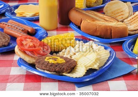 A Hamburger On A Picnic Table Loaded With Food