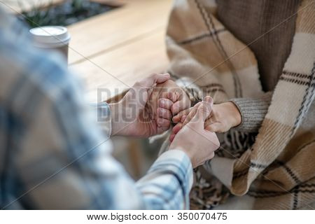 Male Hands And Female Hands Holding Each Other.