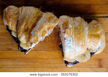 Croissant With Chocolate Butter And Banana On A Wooden Background.