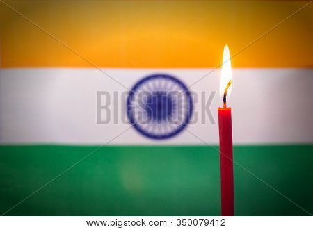 Burning Candle On The Background Of The Flag Of India. The Concept Of Mourning And Sorrow In The Cou