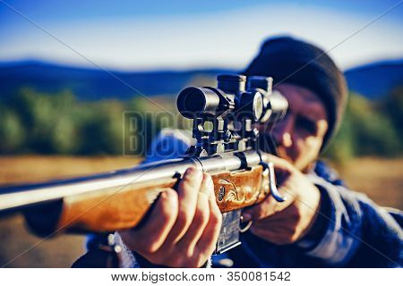 Hunter With Powerful Rifle With Scope Spotting Animals. Hunter With Shotgun Gun On Hunt. Hunter In T