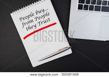 Notebook With The Inscription People Buy From People They Trust On A Black Table.