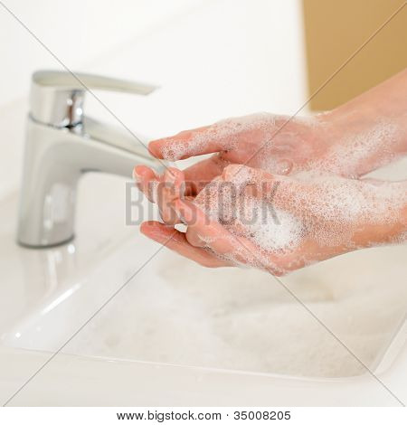 Close-up of washing hands with soap above bathroom sink