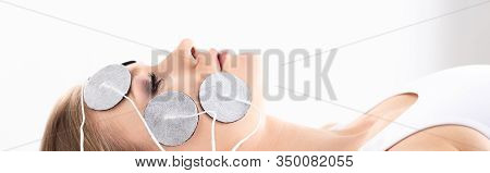 Side View Of Attractive Woman With Electrodes On Face During Facial Electrotherapy On White Backgrou