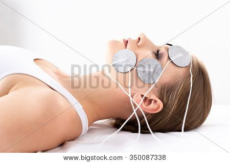 Side View Of Beautiful Woman Lying On Massage Couch During Facial Electrotherapy On White Background