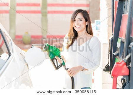 Happy Mid Adult Woman Holding Fuel Pump By Car At Self-service Gas Station