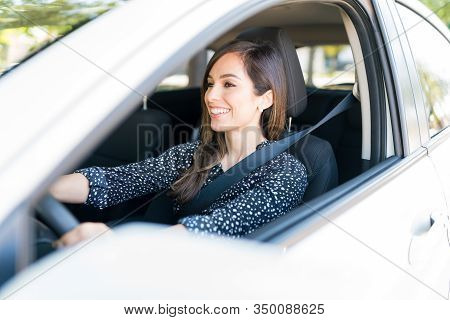 Happy Mid Adult Woman Driving Car Seen Through Window