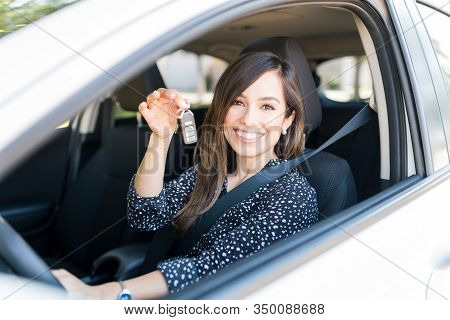 Happy Mid Adult Woman Showing Key While Sitting In New Car