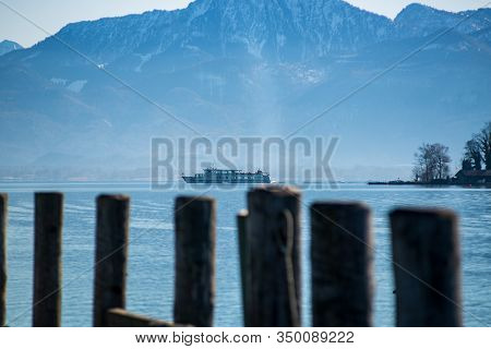 Gstadt,germany- February 8,2020: A Sight Seeing Boat Leaves Frauen Insel On Chiemsee With The Alps I