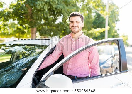 Happy Handsome Hispanic Man Opening Door Of New Car On Sunny Day