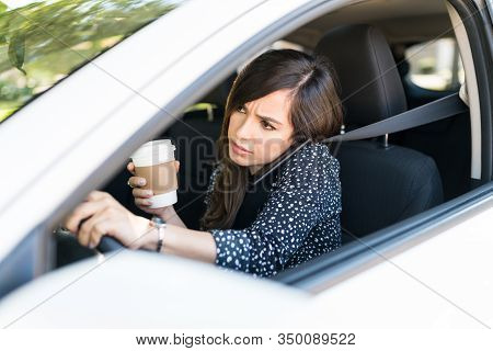 Mid Adult Woman Talking On Mobile Phone While Driving Car