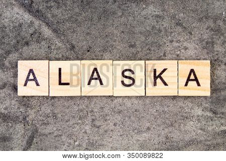 Alaska Word Written On Wood Block, On Gray Concrete Background. Top View.