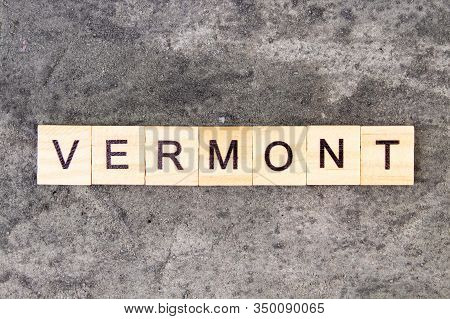 Vermont Word Written On Wood Block, On Gray Concrete Background. Top View.