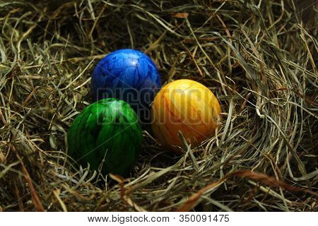 Three Colored Easter Eggs In Hay In The Eastertime