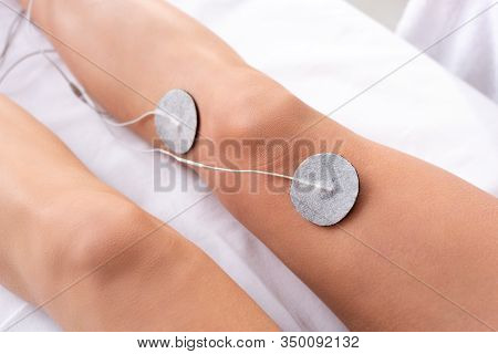 Cropped View Of Woman Lying On Massage Couch During Electrotherapy Of Knee Isolated On Grey