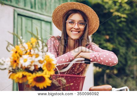 Optimistic Young Woman In Stylish Hat And Glasses Smiling For Camera And Leaning On Bicycle With Flo