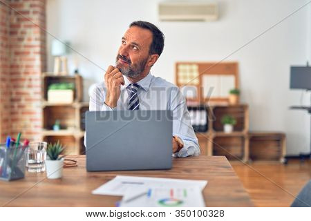 Middle age handsome businessman wearing tie sitting using laptop at the office with hand on chin thinking about question, pensive expression. Smiling with thoughtful face. Doubt concept.