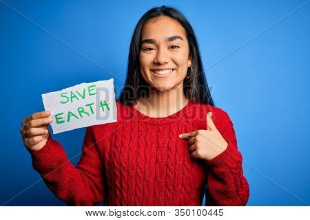 Young beautiful asian woman holding paper asking for save earth and enviroment conservation with surprise face pointing finger to himself