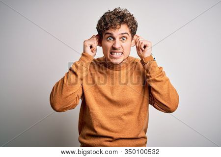 Young blond handsome man with curly hair wearing casual sweater over white background Smiling pulling ears with fingers, funny gesture. Audition problem