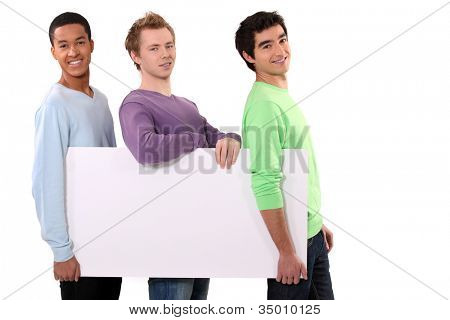 Three friends holding blank poster